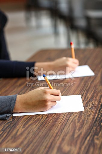 820495452 istock photo Female writing hands on a desk in classroom 1147009421
