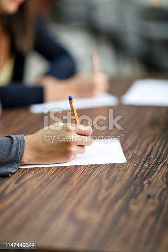 820495452 istock photo Female writing hands on a desk in classroom 1147449344