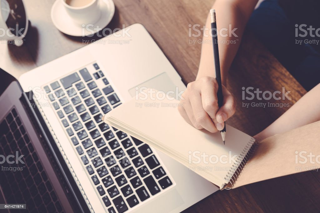 Female writing information on paper in workplace. office concept. stock photo