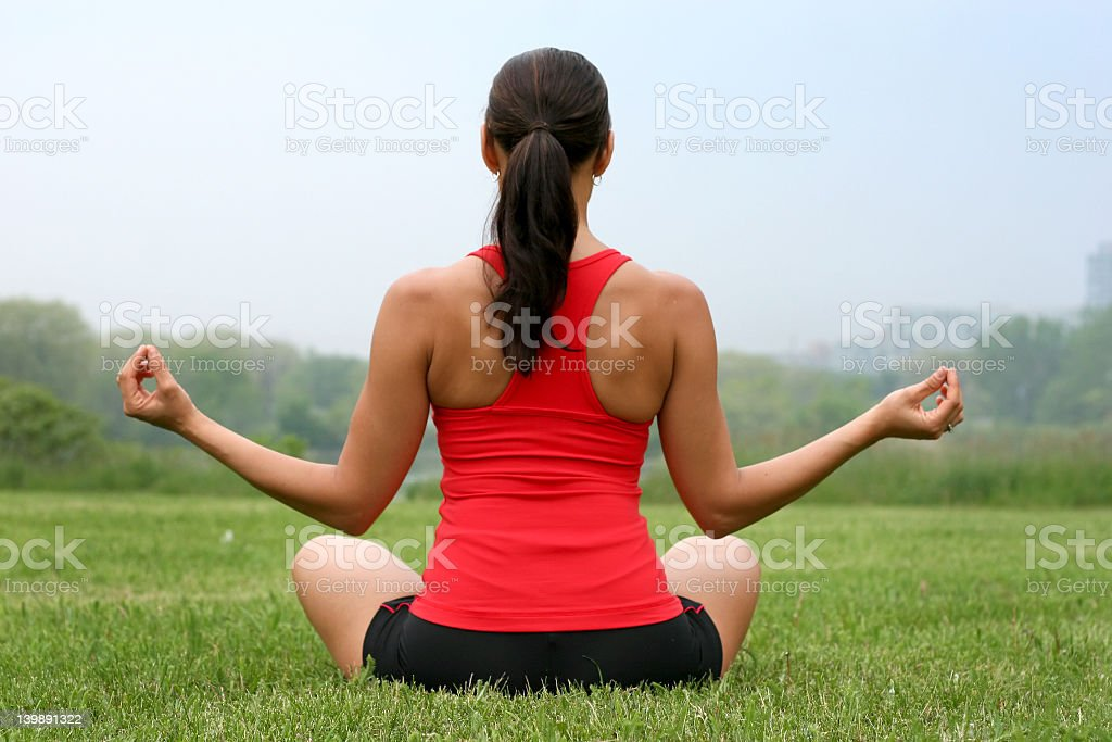 A female yoga instructor sitting in a grass field royalty-free stock photo