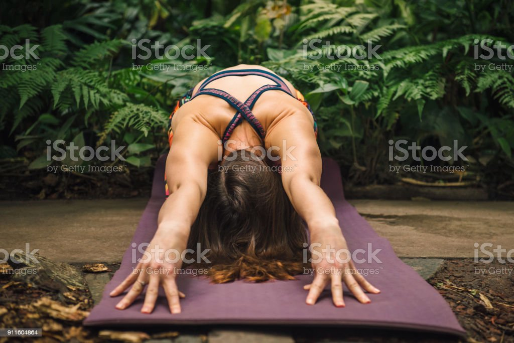 Female yoga instructor stretching on a mat stock photo