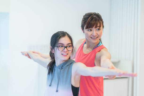 Female yoga instructor teaching yoga A female yoga instructor is teaching yoga. yoga instructor stock pictures, royalty-free photos & images