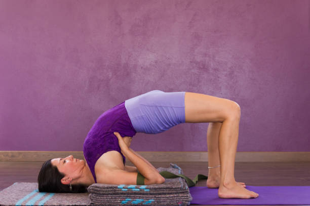 Female yogi in setu bandha sarvangasana over purple wall stock photo