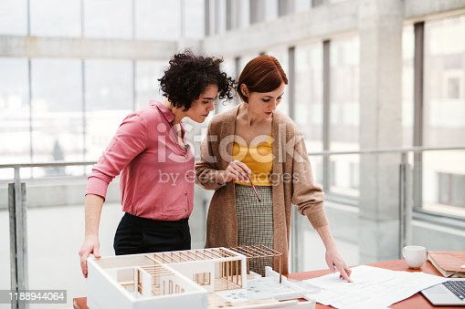 Two female young architects with model of a house standing in office, working and talking.