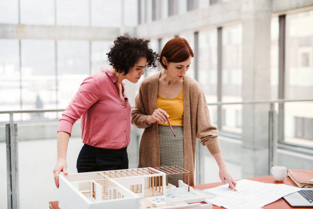 weibliche junge architekten mit modell eines hauses im büro stehen, reden. - architekturberuf stock-fotos und bilder