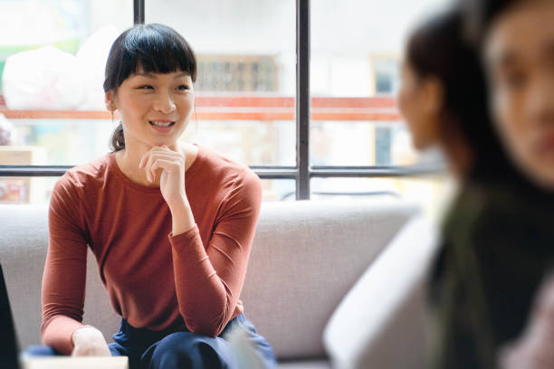Weiblicher junger asiatischer Unternehmer lächelt und diskutiert Ideen mit Kollegin – Foto