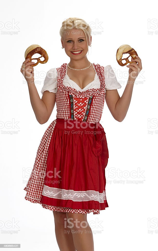 Female young blond beauty portrait with dirndl showing pretzels royalty-free stock photo