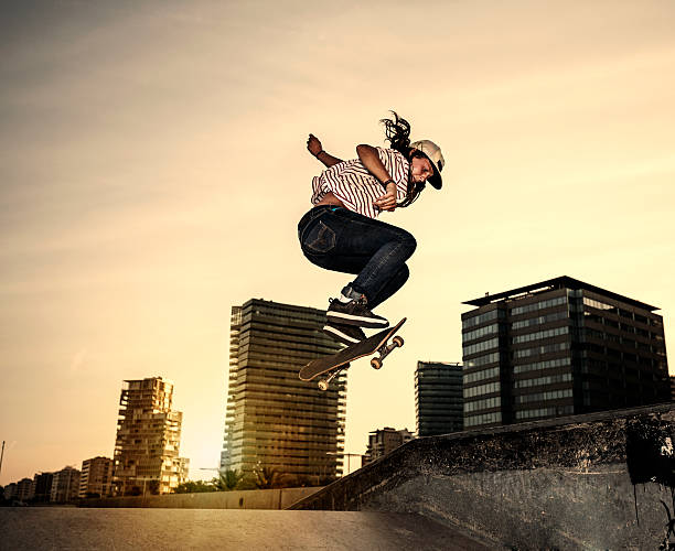 female young skateboarder jumping in skatepark in the city - skateboarding stock pictures, royalty-free photos & images
