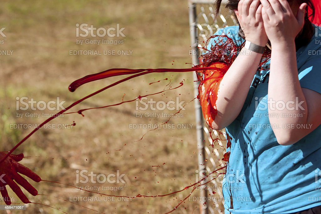 Female Zombie Gets Fake Blood Splattered on Her Clothes stock photo