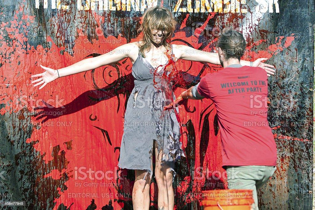 Female Zombie Gets Fake Blood Splattered On Her Dress stock photo
