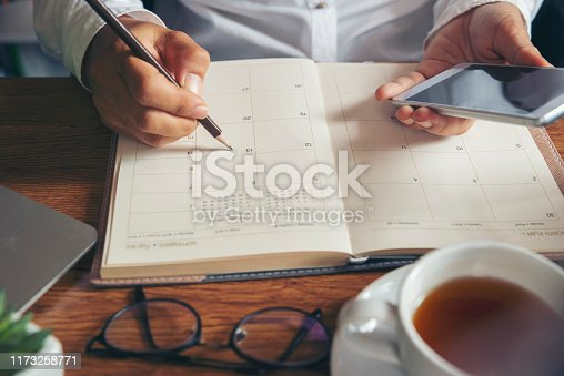 On 2020 Calendar book,Female'hand of planner writing daily appointment.Woman mark and noted schedule(holiday trip) on diary at office desk.Calendar reminder event for planner concept