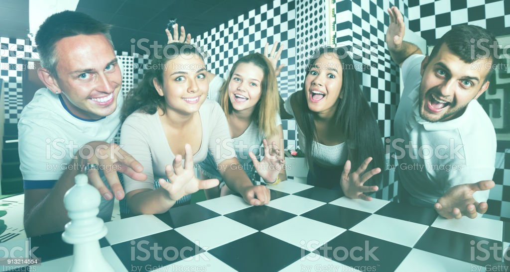 females and males  on chessboard in quest room stock photo