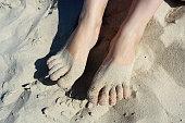 Female's bare feet in white sand on beach.