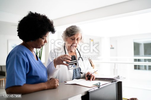istock Females doctor and nurse talking in hospital secretary and walking 1201457958