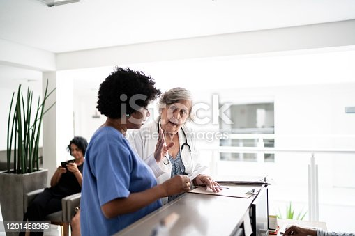 istock Females doctor and nurse talking in hospital secretary and walking 1201458365