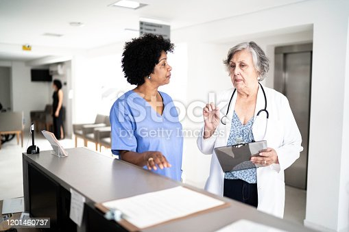 istock Females doctor and nurse talking in hospital secretary and walking 1201460737