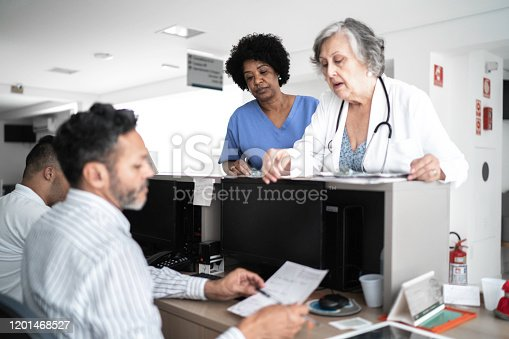 istock Females doctor and nurse talking in hospital secretary and walking 1201468527