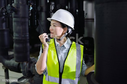 Close-up of one females engineer talking at black pipeline backgrounds.