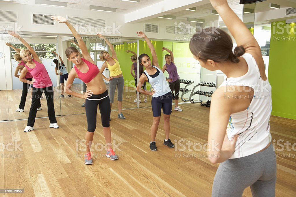 Females exercising with instructor in studio with mirrors royalty-free stock photo