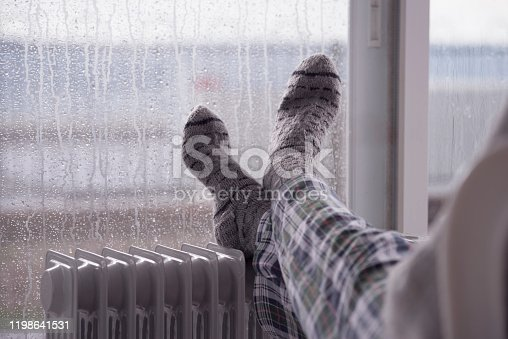 Woman wearing gray pair of woolen socks, warming cold feet in front of the heater, staying at home in the rain winter season.