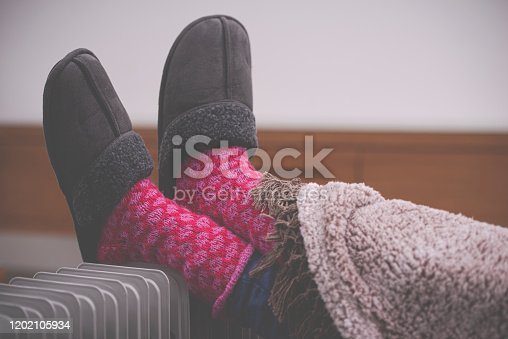 Female's feet with slippers lying on radiator heater in the living room. Legs covered with a warm blanket. The woman staying at home in the winter season.