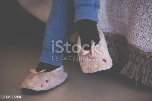 Close up female's feet with slippers sitting on a sofa in the living room. Woman's feet wearing slippers decorated with polka dots and ribbon bow.