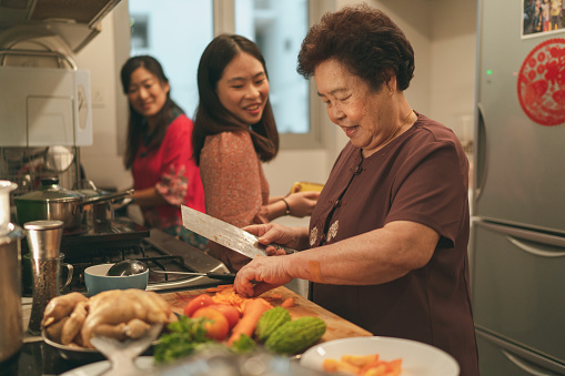 Females from a multi-generation Asian family in a kitchen during the preparation of reunion dinner on Chinese New Year's eve