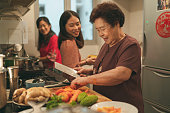 istock Females from a multi-generation Asian family in a kitchen during the preparation of reunion dinner 1288744224
