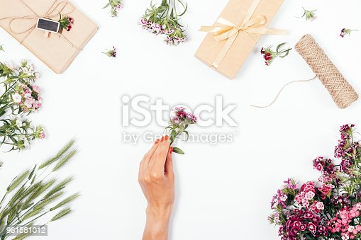 istock Female's hand holding a small flower among the bouquets 961581012
