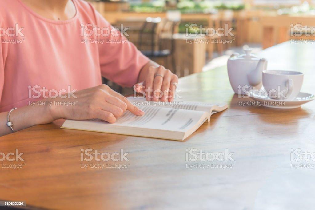 Females hand reading book, having tea outdoors stock photo