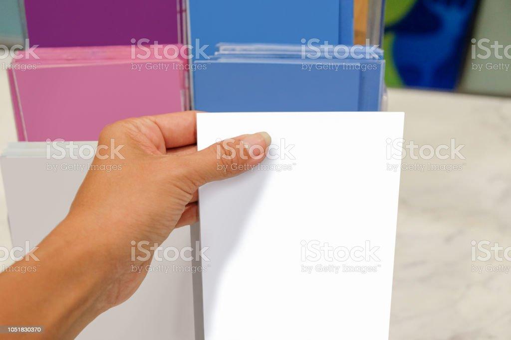 Females hand taking brochure stock photo
