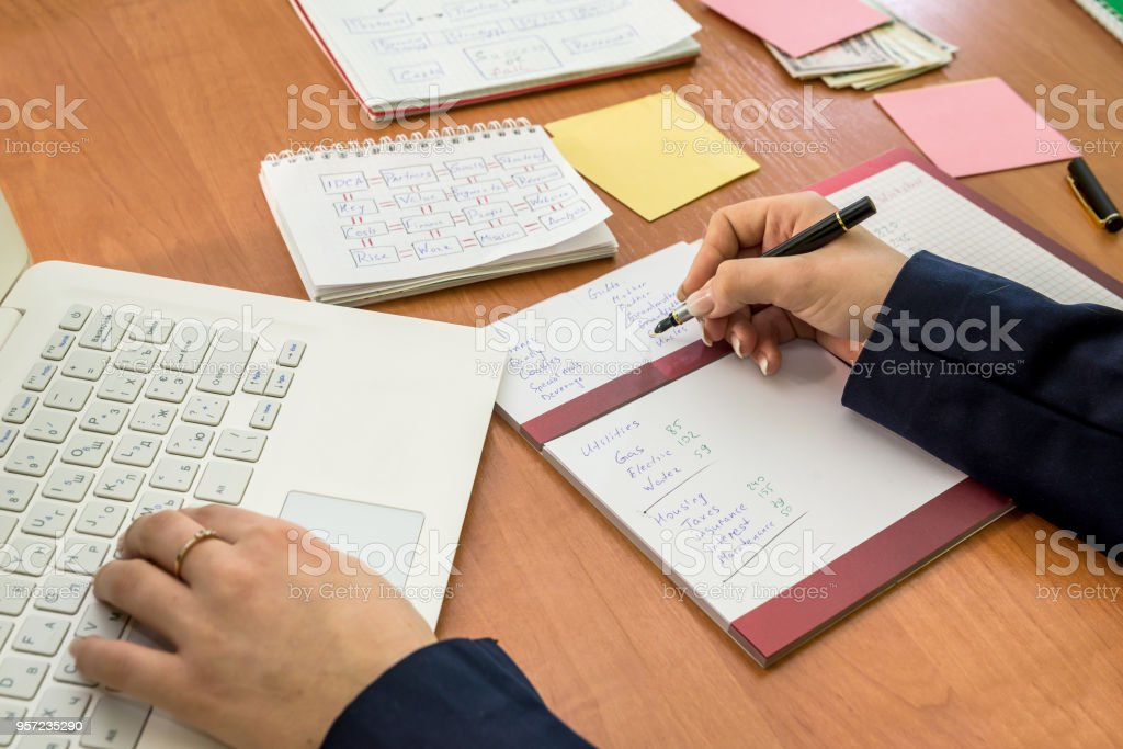 female's hand working in laptop and monthly budget stock photo