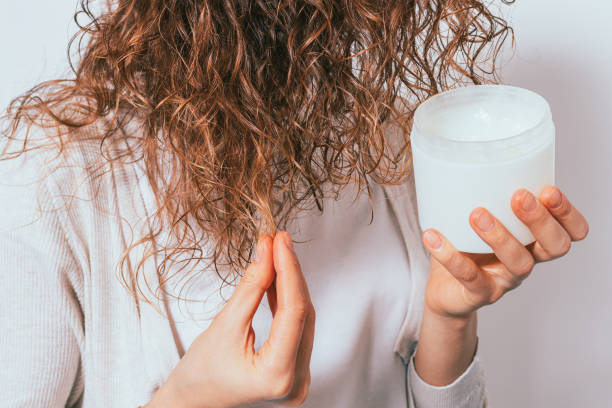 Female's hands apply cosmetic coconut oil stock photo