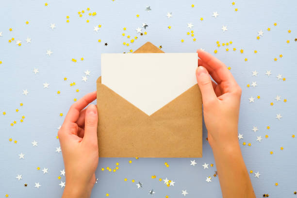 female's hands holding kraft paper envelope letter with blank white card mockup over pastel blue background with golden confetti stars. christmas, new year, winter holidays and birthday concept. - приглашение стоковые фото и изображения