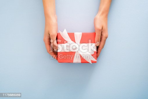 Female's hands holding red gift box with white ribbon bow on pastel blue background. Christmas, New Year, Valentine's day and birthday concept. Minimal flat lay style composition, top view, overhead