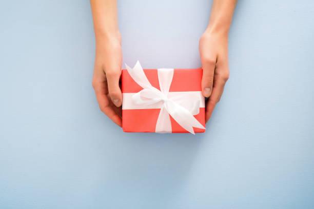 kobiece ręce trzymające czerwone pudełko z białą wstążką na pastelowym niebieskim tle. boże narodzenie, nowy rok, walentynki i koncepcja urodzin. minimalna płaska kompozycja stylu lay, widok z góry, nad głową - gift zdjęcia i obrazy z banku zdjęć