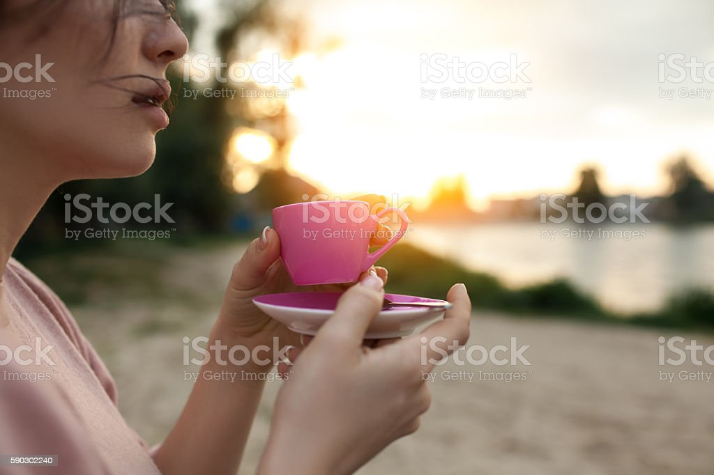 female's hands keep cup of coffee near lake or river; Стоковые фото Стоковая фотография