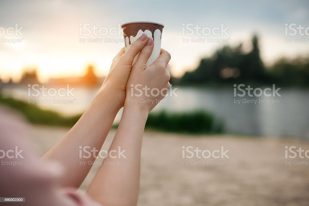 females hands keep paper cup coffee near lake or river; royaltyfri bildbanksbilder