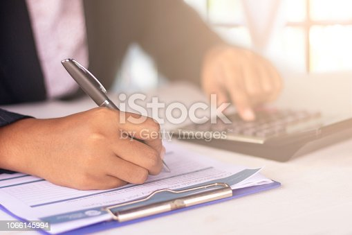 istock Female's hands signing on health claim form and calculator at office, clinic, hospital 1066145994