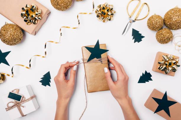 weiblichen händen geschenkbox mit bindfaden umwickeln - damen top gold stock-fotos und bilder