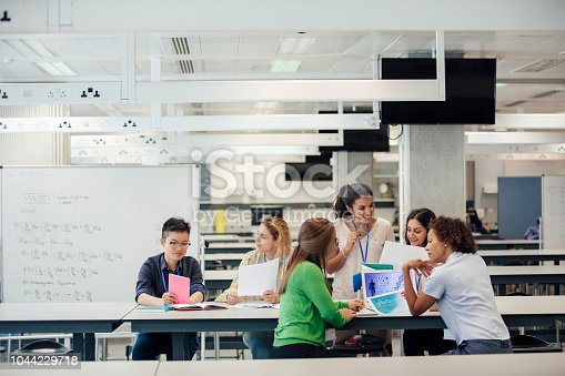 A laboratory classroom with a group of female science students working. The classmates are discussing work, and debating ideas and opinions. This architecture is well designed and versatile, allowing for changing demands in this education space. There is a whiteboard with mathematic equations on it, behind the positive animated group. The women are of differing ethnicities.