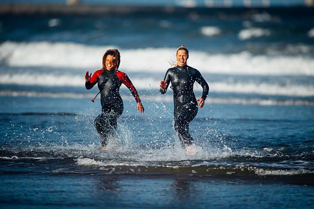 females in wetsuits running out of the sea - girl power provérbio em inglês - fotografias e filmes do acervo