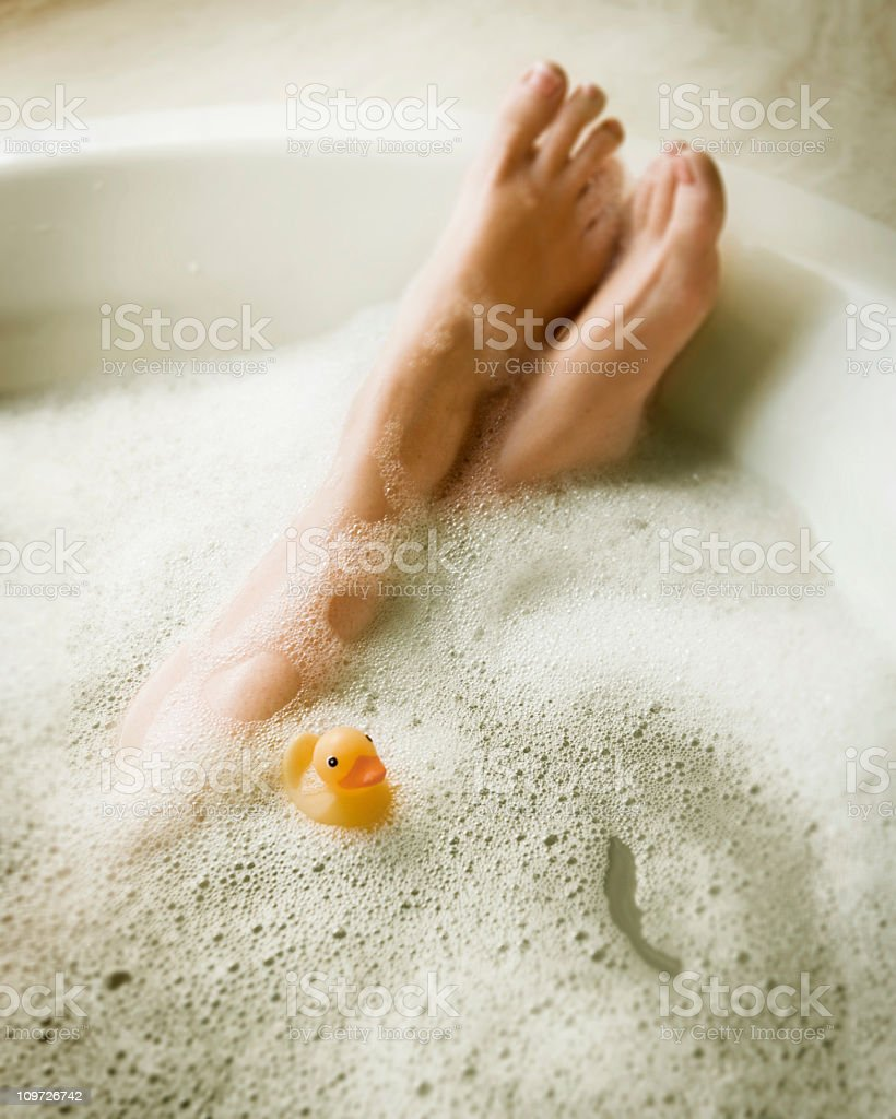 Femmine di gambe in Bubblebath con giallo Rubber Ducky - foto stock