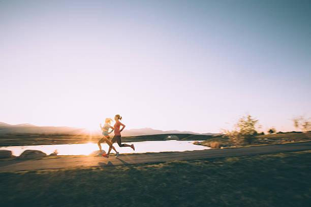 Mujeres corriendo en camino durante la puesta de sol en Utah - foto de stock