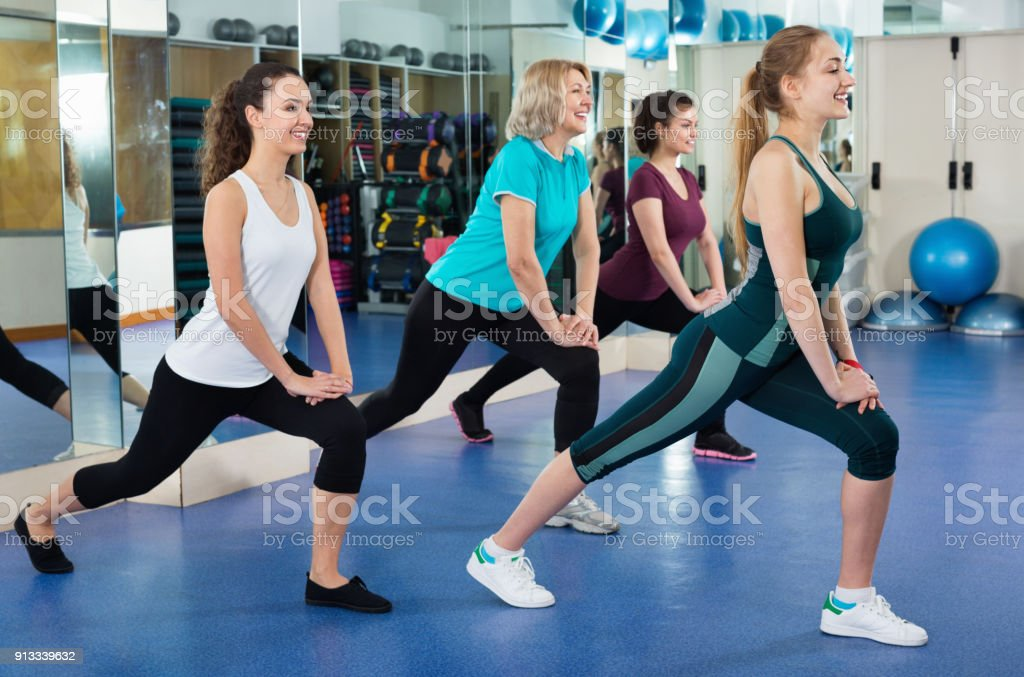females working out at aerobic class in modern gym for women stock