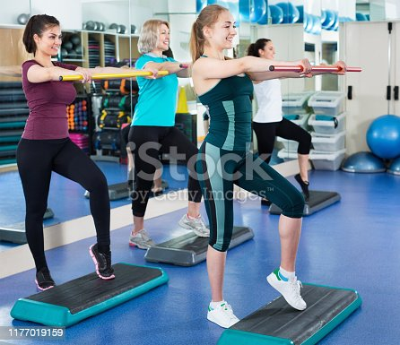 Positive happy females working out on aerobic step platform in modern gym