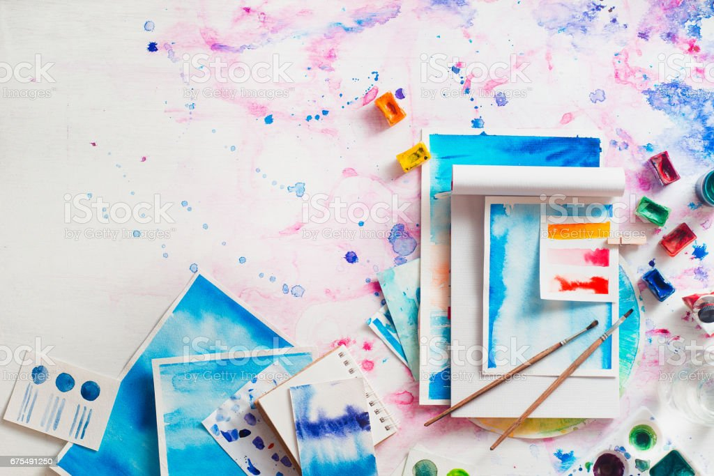 Feminine artist workplace with watercolor and notepads stock photo