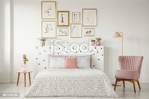 istock Feminine bedroom interior with a double bed with dotted sheets, armchair, art collection and plants 991205262