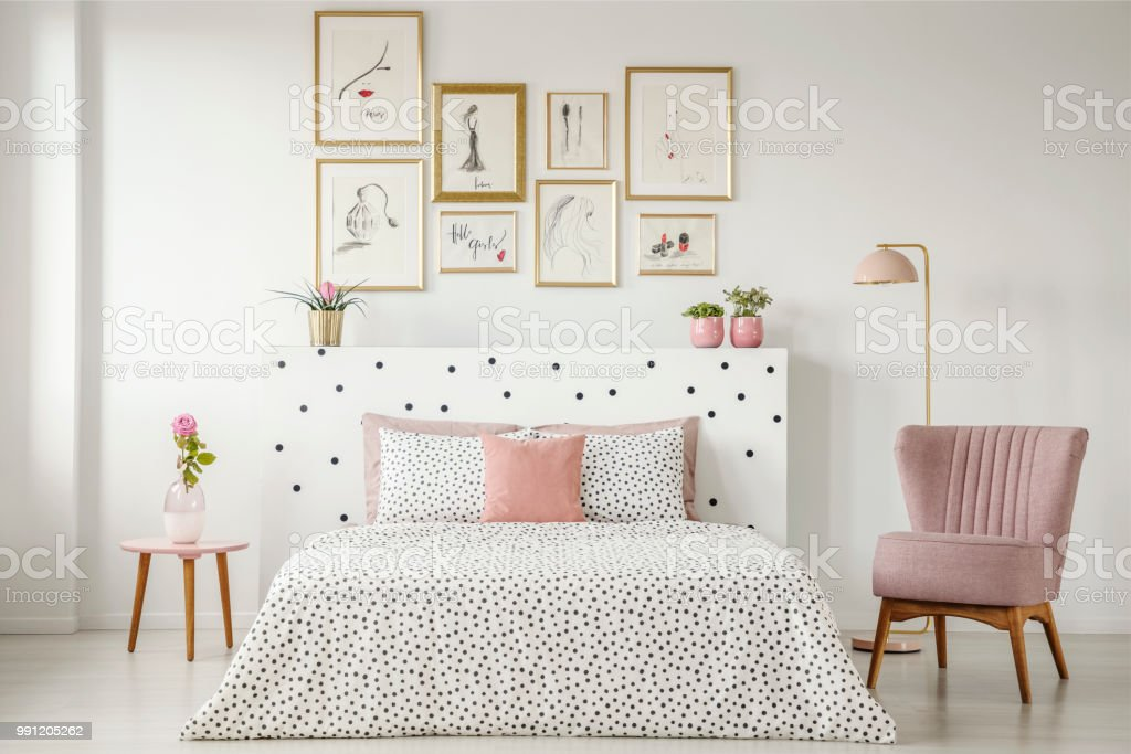 Feminine bedroom interior with a double bed with dotted sheets, armchair, art collection and plants stock photo