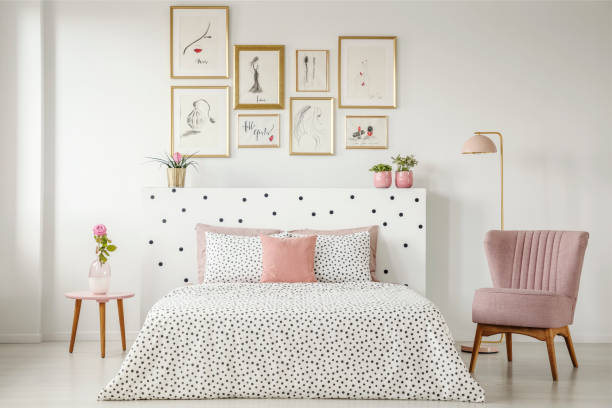 Feminine bedroom interior with a double bed with dotted sheets, armchair, art collection and plants Feminine bedroom interior with a double bed with dotted sheets, armchair, art collection and plants bedroom stock pictures, royalty-free photos & images